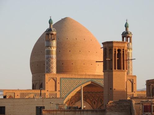 Wüstenbewohner kennen sich aus mit Ventilation: Im Vordergrund ein Bādgir, ein Windfänger, der die Räume angenehm runterkühlt. Im Hintergrund die große Moschee in Yazd.